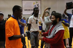 O refugiado sírio Adbul (à direita), um dos responsáveis pela organização da Copa de Integração, entre troféus ao final da Copa da Integração. Foto: SESC-SP/Junior Pacheco